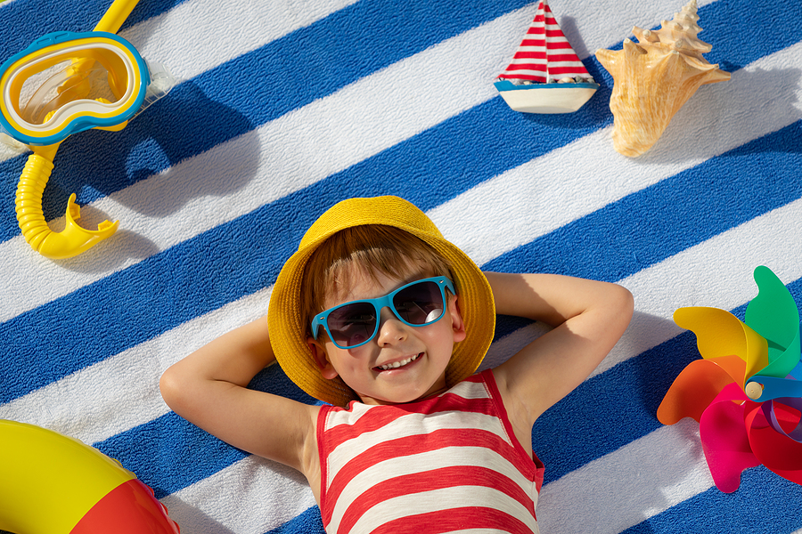Happy small boy lying on blue and white striped cotton beach towel with beach toys around him