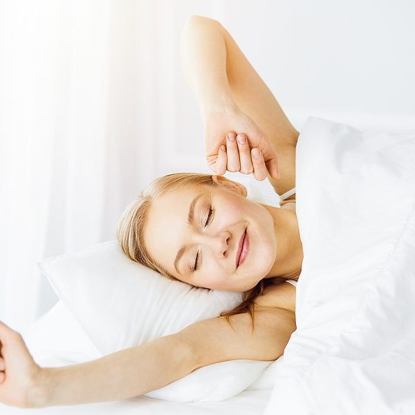 smiling blonde woman waking up in bed stretching comfortable after sleeping well
