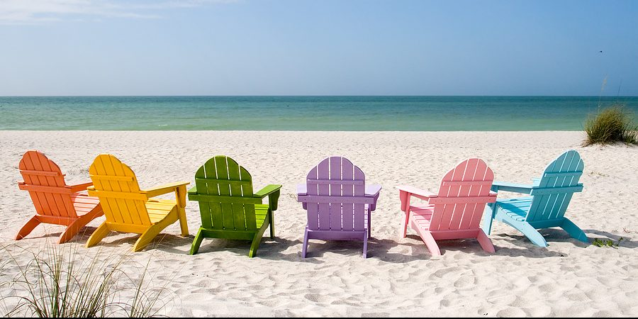 summer beach calm ocean view with six colorful wooden beach chairs