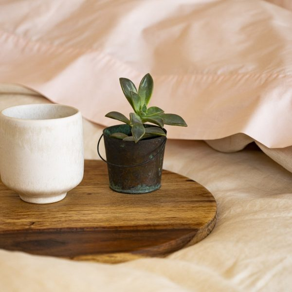 close up of soft bed with linen duvet cover and pink bedding with mug of hot coffee and a small plant on a wooden tray
