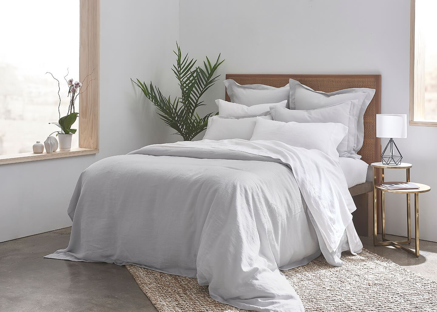 gray linen duvet cover on a luxury double bed with plush pillows in a minimalist bedroom